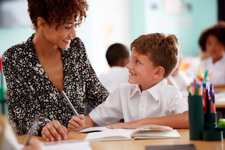 Teacher Helping Pupil With Classwork